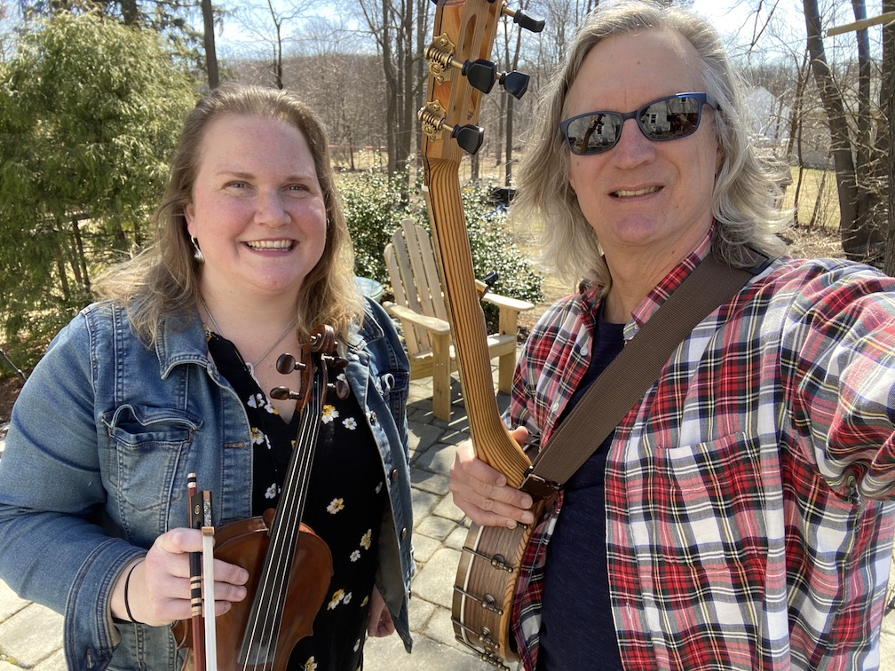 photo of Long Lost String Band - Anne Rouillard with a fiddle on the left and Chris Reckling with a banjo on the right.